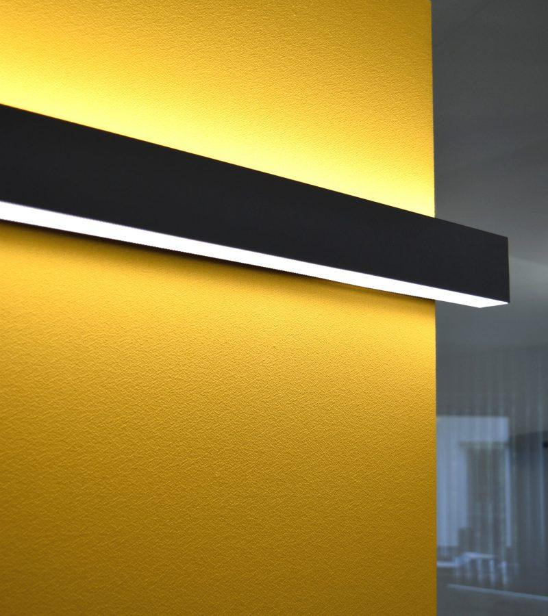 Kombination aus Schallabsorber Wand in gelb mit Beleuchtung mit PreGlass Trennwandsystem