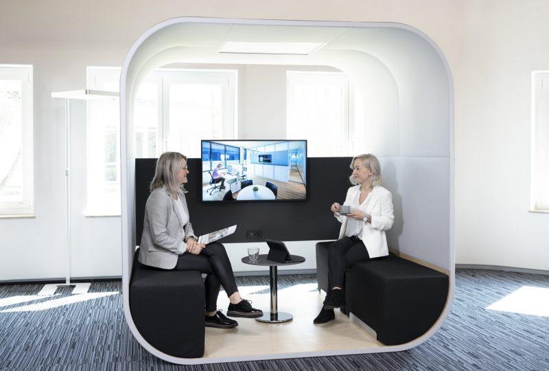 Zwei Personen kommunizieren in akustisch wirksamer Raum in Raum Lösung Prespace Tube